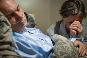 Woman grieving a dying man