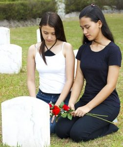 Two women kneeling at a grave