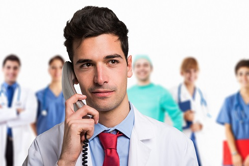 Nurse manager on the phone with health care providers in the background
