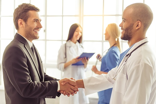 Male Nurse Manager shaking hands with a male physician nurses in the background