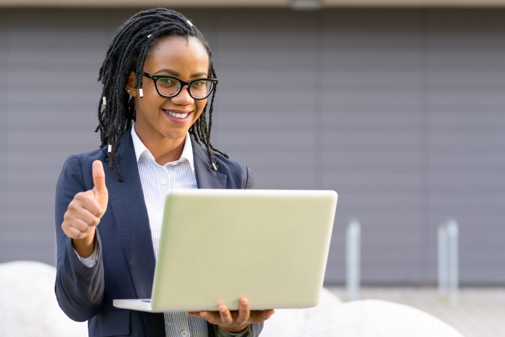 Smiling woman with laptop giving thumb up